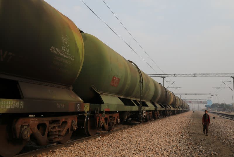 A boy walks past an oil tanker train stationed at a railway station in Ghaziabad