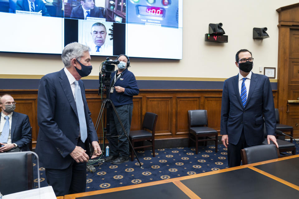 Federal Reserve Chair Jerome Powell, left, and Treasury Secretary Steven Mnuchin arrive for a House Financial Services Committee hearing on Capitol Hill in Washington, Wednesday, Dec. 2, 2020. (Jim Lo Scalzo/Pool via AP)