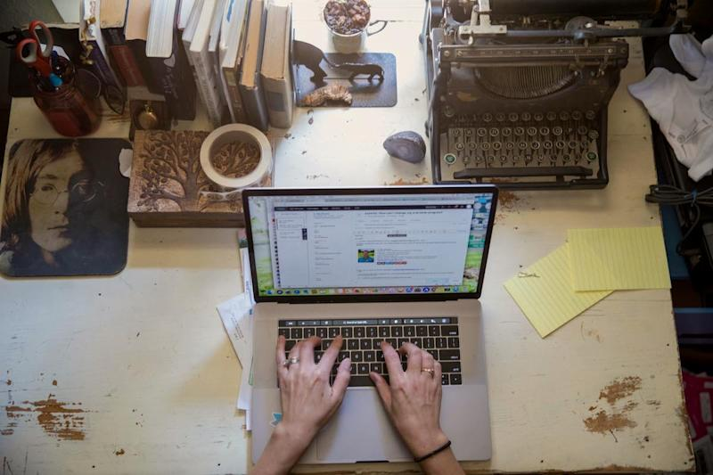 a woman typer on her laptop at her desk from home