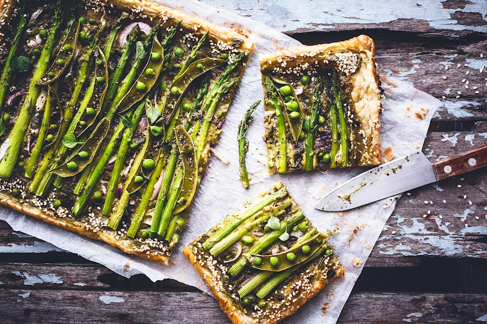 Asparagus tastes delicious on a simple ready-roll puff pastry tart with peas, pesto and cheese. (Getty Images)