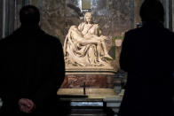 "Visitors admire the marble sculpture ""The Piety"", made in 1499 by Italian sculptor Michelangelo Buonarroti, inside St. Peter's Basilica, at the Vatican, Monday, Dec. 14, 2020. Like elsewhere in Europe, museums and art galleries in Italy were closed this fall to contain the spread of COVID-19, meaning art lovers must rely on virtual tours to catch a glimpse of the treasures held by famous institutions such as the Uffizi in Florence and the Vatican Museums in Rome. However, some exquisite gems of Italy's cultural heritage remain on display in real life inside the country's churches, some of which have collections of renaissance art and iconography that would be the envy of any museum. (AP Photo/Andrew Medichini)"