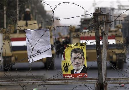 A poster of ousted Egyptian President Mursi is pictured on barbed wires during a protest by his supporters in Cairo
