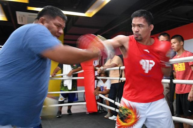 Manny Pacquiao spars with childhood friend and long-time assistant trainer Buboy Fernandez. July's bout will be the 'basis' for a retirement call, said the fighter (AFP Photo/TED ALJIBE)