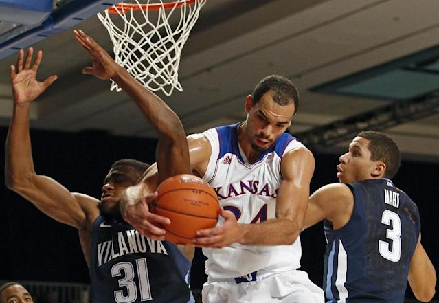 Kansas's Perry Ellis, center, pulls down a rebound against Villanova's Jamari Traylor, left, and Andrew White during the first half of an NCAA college basketball game in Paradise Island, Bahamas, Friday, Nov. 29, 2013. (AP Photo/Bahamas Visual Services, Dante Carrer)
