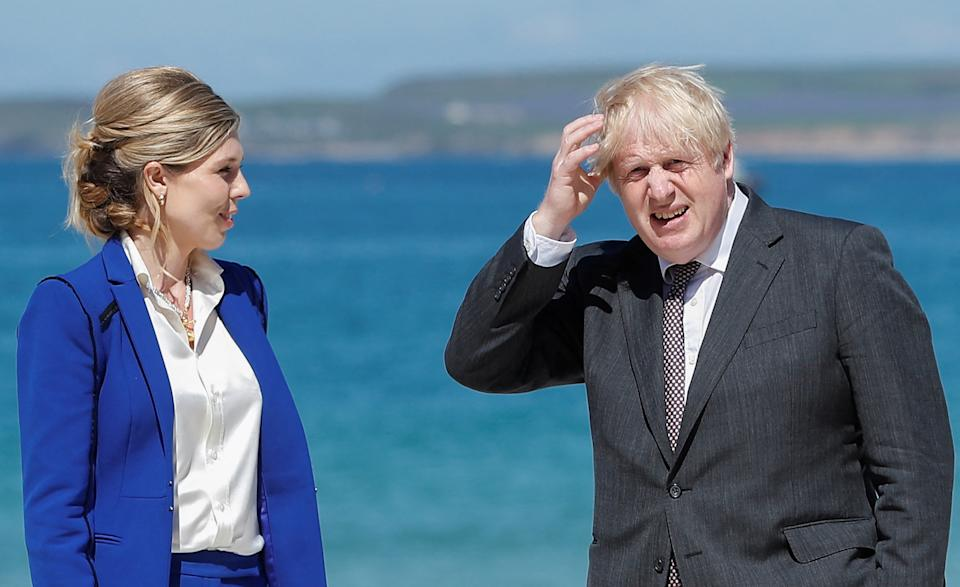 Britain's Prime Minister Boris Johnson and his wife Carrie Johnson wait to welcome leaders during the G7 summit in Carbis Bay, Cornwall on June 12, 2021. - G7 leaders from Canada, France, Germany, Italy, Japan, the UK and the United States meet this weekend for the first time in nearly two years, for three-day talks in Carbis Bay, Cornwall. (Photo by PETER NICHOLLS / POOL / AFP) (Photo by PETER NICHOLLS/POOL/AFP via Getty Images)