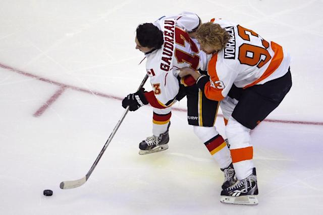 Calgary Flames' Johnny Gaudreau (13), is helped by Philadelphia Flyers' Jakub Voracek (93), during the Breakaway competition at the NHL All-Star hockey skills competition in Columbus, Ohio, Saturday, Jan. 24, 2015. (AP Photo/Gene J. Puskar)