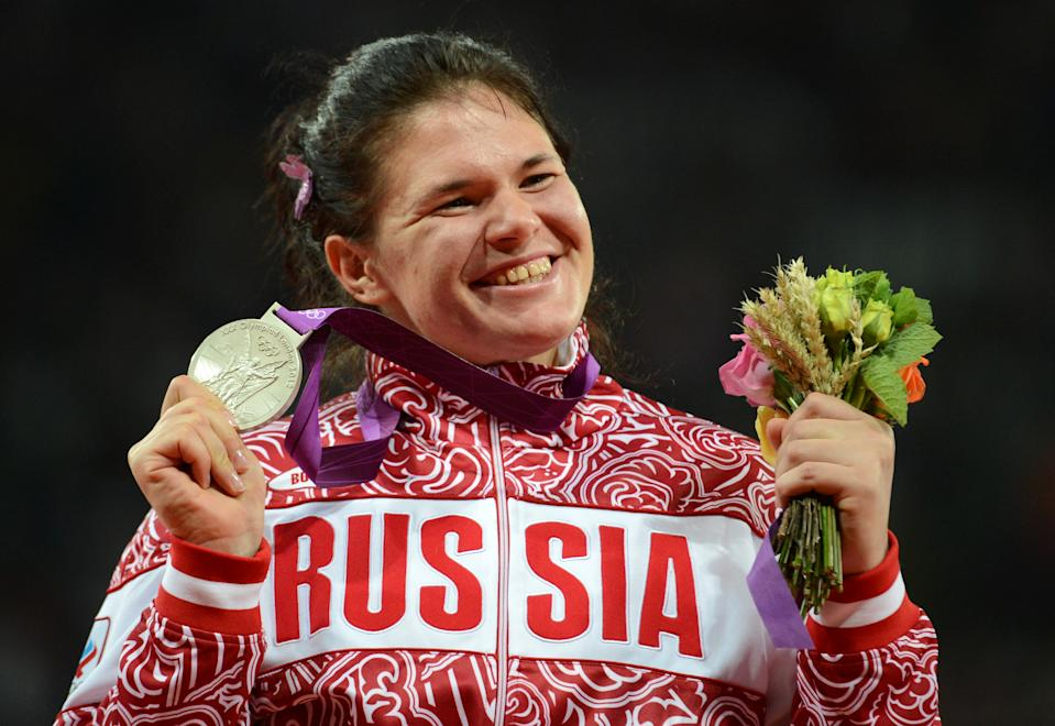 Silver medalist Russia's Darya Pishchalnikova celebrates on the podium of the women's discus throw at the athletics event of the London 2012 Olympic Games on August 4, 2012 in London.  AFP PHOTO / JOHANNES EISELE        (Photo credit should read JOHANNES EISELE/AFP/GettyImages)