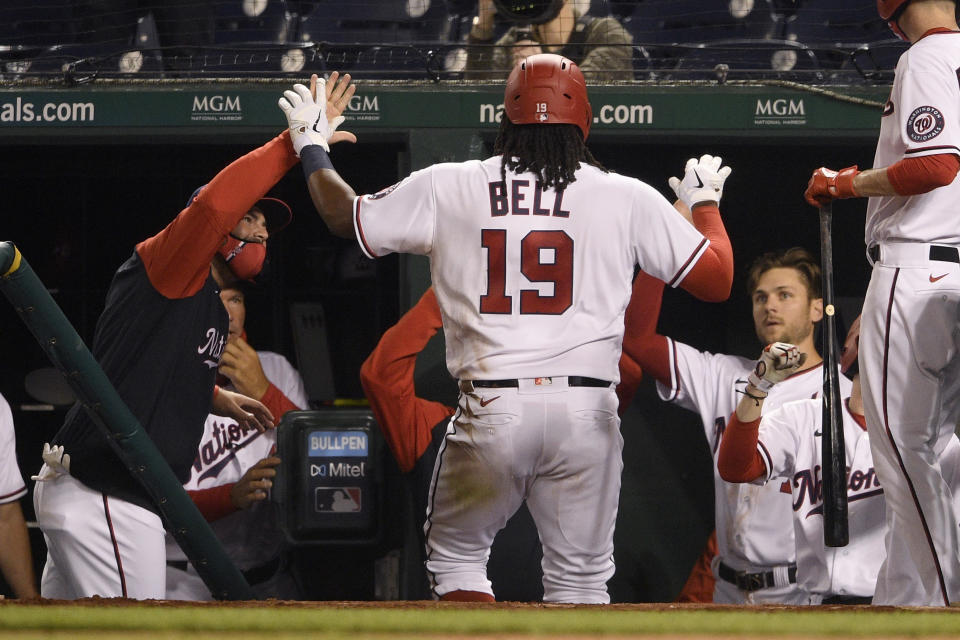 Washington Nationals' Josh Bell (19) returns to the dugout after hitting a home run during the sixth inning of the team's baseball game against the St. Louis Cardinals, Tuesday, April 20, 2021, in Washington. (AP Photo/Nick Wass)
