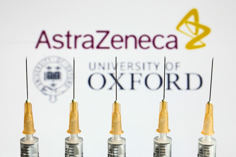 Medical syringes are seen with AstraZeneca and University of Oxford logos displayed on a screen in the background in this illustration photo taken in Krakow, Poland on April 14, 2021. (Photo by Jakub Porzycki/NurPhoto via Getty Images)