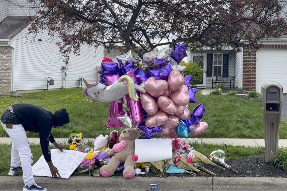 A man adjusts a sign near a memorial at the scene in the Columbus, Ohio neighborhood Friday, April 23, 2021 where 16-year-old Ma'Khia Bryant was fatally shot by police as she swung at two other people with a knife on Tuesday, April 20. Three Democratic members of Congress are asking the U.S. Department of Health and Human Services to investigate the foster care circumstances leading up to the fatal police shooting of Bryant. U.S. Rep. Joyce Beatty and Sen. Sherrod Brown of Ohio, along with Oregon Rep. Ron Wyden, penned a letter Tuesday, June 1, 2021 on behalf of Bryant's parents, requesting for the federal agency to look into the teen's experience through the foster care system. (AP Photo/Farnoush Amiri)