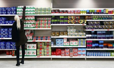 A shopper reaches for a box of tea in a supermarket in London