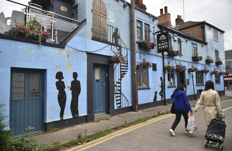 People walks past the Black Horse pub inside the lock down zone, in Leicester, England, Saturday July 4, 2020. England is embarking on perhaps its biggest lockdown easing yet as pubs and restaurants have the right to reopen for the first time in more than three months. One city that is not participating in the easing is Leicester, in central England. The government reimposed lockdown restrictions there, including the closure of schools and nonessential shops, after a spike in new infections. (AP Photo/Rui Vieira)