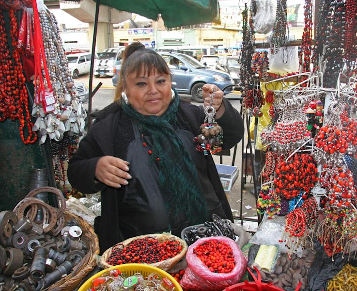 In this June 7, 2013 photo, Beatrice Torre sells items made from huayruro hembra and el macho, which are bright red and black Amazonian seeds, outside the witches market in Lima, Peru. (AP Photo/Jody Kurash)