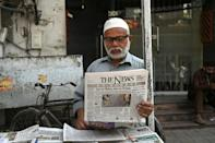 A man reads a morning newspaper showing Joe Biden, at a stall in Pakistan's Lahore
