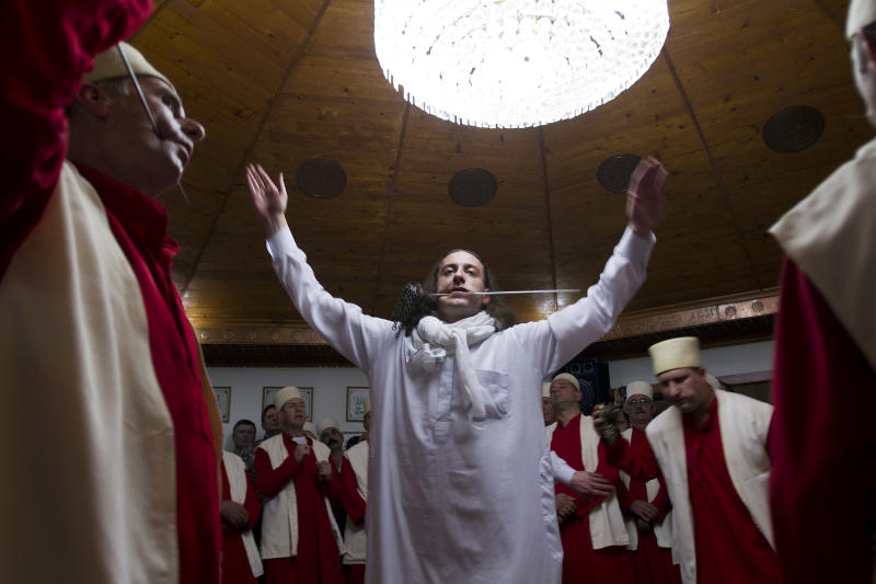 Kosovo dervishes, followers of Sufism, a mystical form of Islam that preaches tolerance and a search for understanding, take part in a ceremony marking Nowruz in the prayer room in the town of Gjakova on Thursday, March 21, 2013. The Kosovo dervish community carries on centuries-old mystical practices, such as self-piercing with needles and knives as a way to earn salvation and find the path to God. ( AP Photo / Visar Kryeziu )