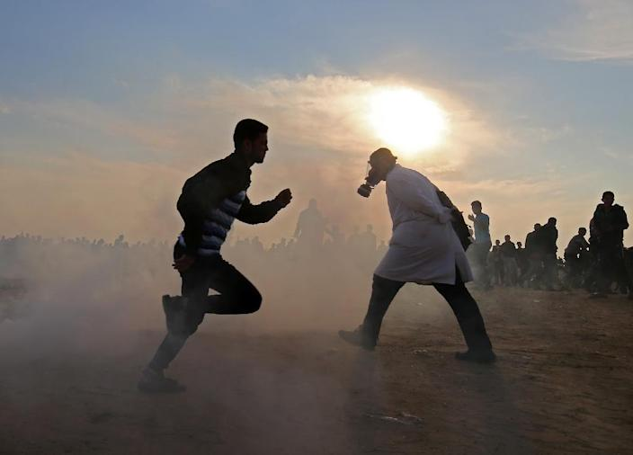 Palestinians run for cover from tear gas during clashes near the border between Israel and Khan Yunis in the southern Gaza Strip on November 9, 2018 (AFP Photo/SAID KHATIB)
