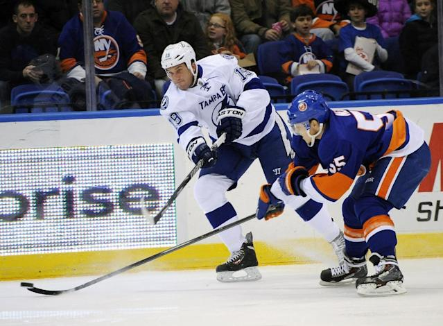 Tampa Bay Lightning B.J. Crombeen (19) shoots the puck past New York Islanders' Aaron Ness (55) in the first period of an NHL hockey game on Tuesday, Dec. 17, 2013, in Uniondale, N.Y. (AP Photo/Kathy Kmonicek)