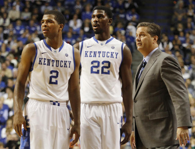 Kentucky head coach John Calipari, right, confers with Aaron Harrison (2) and Alex Poythress (22) during the second half of an NCAA college basketball game against Eastern Michigan, Wednesday, Nov. 27, 2013, in Lexington, Ky. Kentucky won 81-63. (AP Photo/James Crisp)