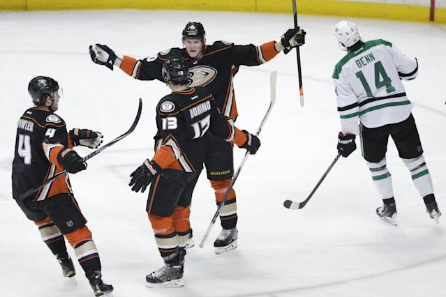 Anaheim Ducks' Nick Bonino(13) celebrates his goal with Cam Fowler(4) and Corey Perry(10) as Dallas Stars' Jamie Benn(14) skates past them in the first period of Game 5 of the first-round NHL hockey Stanley Cup playoff series on Friday, April 25, 2014, in Anaheim, Calif. (AP Photo/Jae C. Hong)