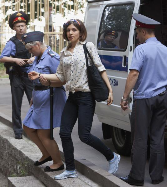 Nadezhda Tolokonnikova, center, a member of feminist punk group Pussy Riot is escorted to a court room in Moscow, Russia, Thursday, Aug. 2, 2012. The trio Pussy Riot face up to seven years behind bars after staging a performance in a Moscow cathedral calling on the Virgin Mary to remove President Putin from power. (AP Photo/Alexander Zemlianichenko)