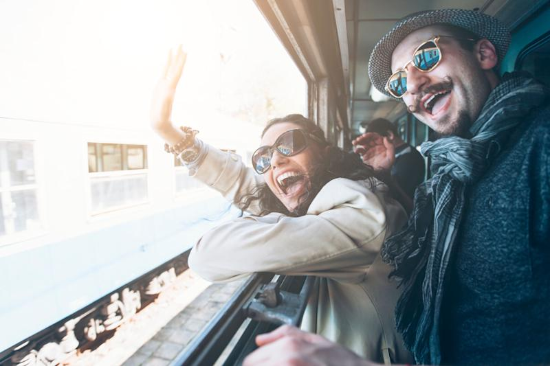 People wearing glasses on a train wave goodbye excitedly. Image: Getty