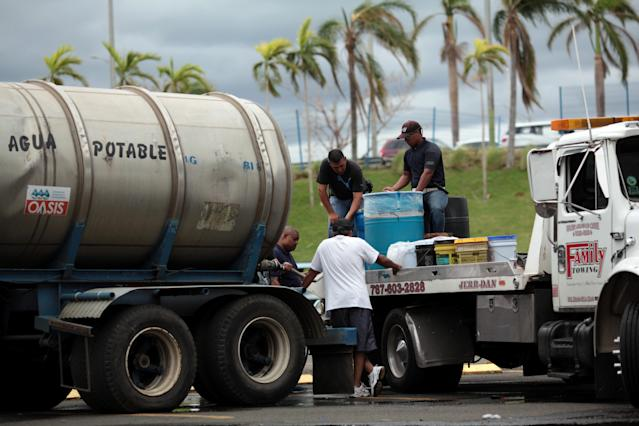 Local residents fill cans of water in Carolina, Puerto Rico, on Saturday. (Alvin Baez / Reuters)