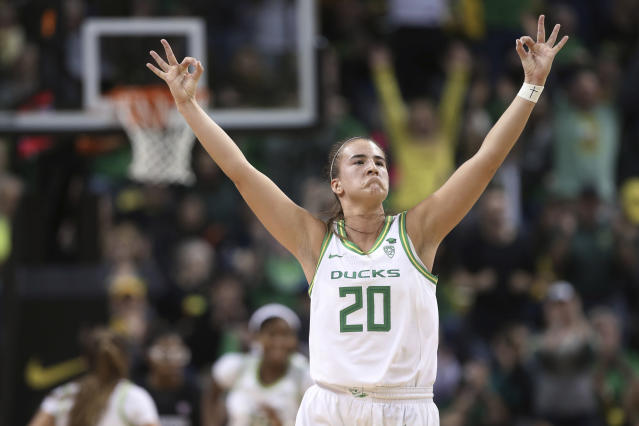 FILE - In this Jan. 16, 2020, file photo, Oregon's Sabrina Ionescu celebrates a 3-point shot against Stanford during the third quarter of an NCAA college basketball game in Eugene, Ore. Ionescu was named to The Associated Press women's All-America first team Thursday, March 19, 2020. The Oregon Ducks senior shattered the NCAA career triple-double mark and became the first player in college history to have 2,000 points, 1,000 rebounds and 1,000 assists.(AP Photo/Chris Pietsch, File)