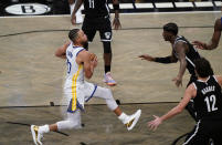 Golden State Warriors guard Stephen Curry (30) drives to the basket with Brooklyn Nets guard Caris LeVert (22) and Joe Harris (12) defending during the 2nd quarter of an opening night NBA basketball game, Tuesday, Dec. 22, 2020, in New York. (AP Photo/Kathy Willens)
