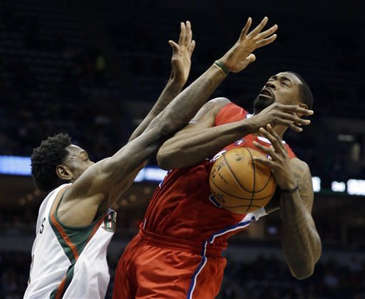 Milwaukee Bucks' Larry Sanders fouls Los Angeles Clippers' DeAndre Jordan as he goes up for a shot during the first half of an NBA basketball game Saturday, Dec. 15, 2012, in Milwaukee. (AP Photo/Morry Gash)