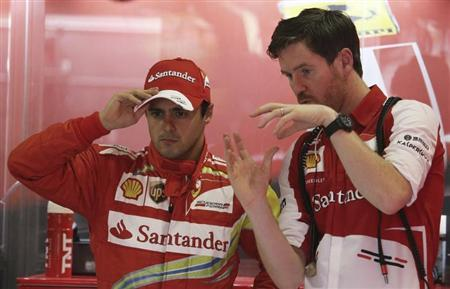 Ferrari Formula One driver Massa talks with a mechanic in the garage before the start of the first free practice session ahead of the Brazilian F1 Grand Prix at the Interlagos circuit in Sao Paulo