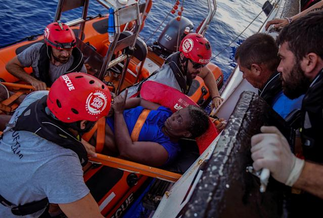 NBA Memphis player Marc Gasol and members of NGO Proactiva Open Arms rescue boat carry an African migrant in central Mediterranean Sea, July 17, 2018. REUTERS/Juan Medina