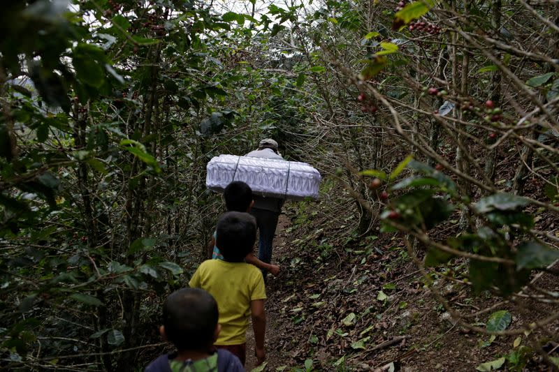 Marvin Roque carries the coffin of his late niece Yesmin Anayeli towards a hilltop for her burial in La Palmilla