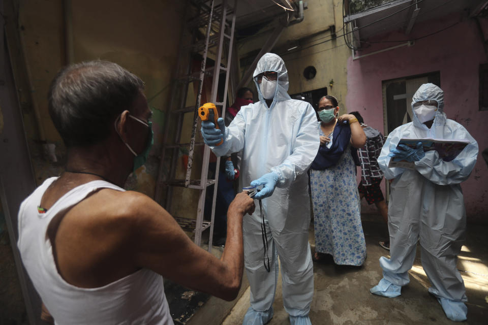 A doctor checks the temperature of a man during a free medical camp in Dharavi, one of Asia's largest slums in Mumbai, India, Saturday, June 20, 2020. India is the fourth hardest-hit country by the COVID-19 pandemic in the world after the U.S., Russia and Brazil. (AP Photo/Rafiq Maqbool)