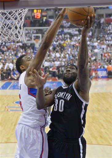 Brooklyn Nets forward Reggie Evans, right, puts up a shot as Los Angeles Clippers center DeAndre Jordan defends during the first half of their NBA basketball game, Saturday, March 23, 2013, in Los Angeles. (AP Photo/Mark J. Terrill)
