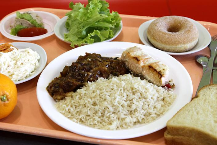 A school lunch consisting of rice, salmon, ratatouille, a slice of bread, a salad with celery and carrots, and an orange and donut is laid out on a tray at the Anne Franck school in Lambersart, northern France, Tuesday, May 6, 2014. (AP Photo/Michel Spingler)