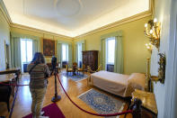 A visitor looks at the pope's bedroom inside the Papal Palace in Castel Gandolfo, some 30 kilometers southeast of Rome, Saturday, May 29, 2021. As Covid-19 restrictions are slowly being lifted in Italy, thousands of people are returning to visit the extensive gardens and apartments at the Papal Palace of Castel Gandolfo in the Alban Hills near Rome, that for hundreds of years have been the summer retreat for Popes seeking to escape the suffocating heat of Rome. (AP Photo/Andrew Medichini)