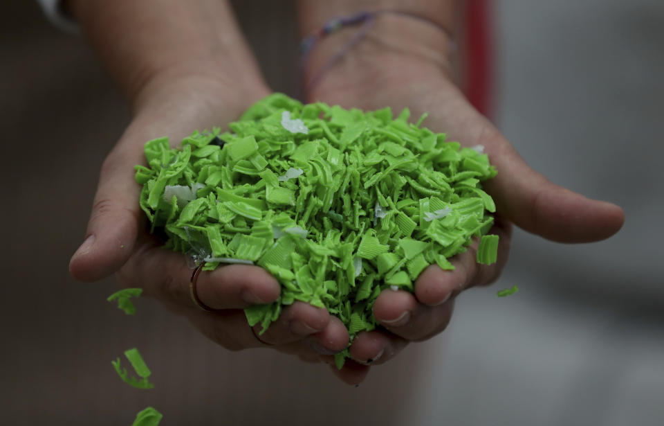 A worker shows shredded bottle caps that will be transformed into raw material to make different plastic articles at the Colorplastic company in Bogota, Colombia, Friday, April 9, 2021. Sajú is a company that makes sunglasses from old plastic lids, like those on soda bottles. The company buys bottle tops that have been turned into small pellets by a recycling plant, melts down the material and injects it into molds to produce colorful frames. Dark lenses are then mounted on the frames, to make shades that are sold at Sajú's stores for about $40 each. (AP Photo/Fernando Vergara)