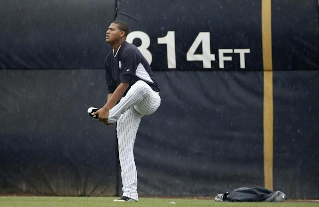 New York Yankees starting pitcher Ivan Nova warms out in the outfield before a spring exhibition baseball game against the Miami Marlins in Tampa, Fla., Saturday, March 29, 2014. Nova had been scheduled start Saturday, but rain forced the game to be canceled. (AP Photo/Kathy Willens)