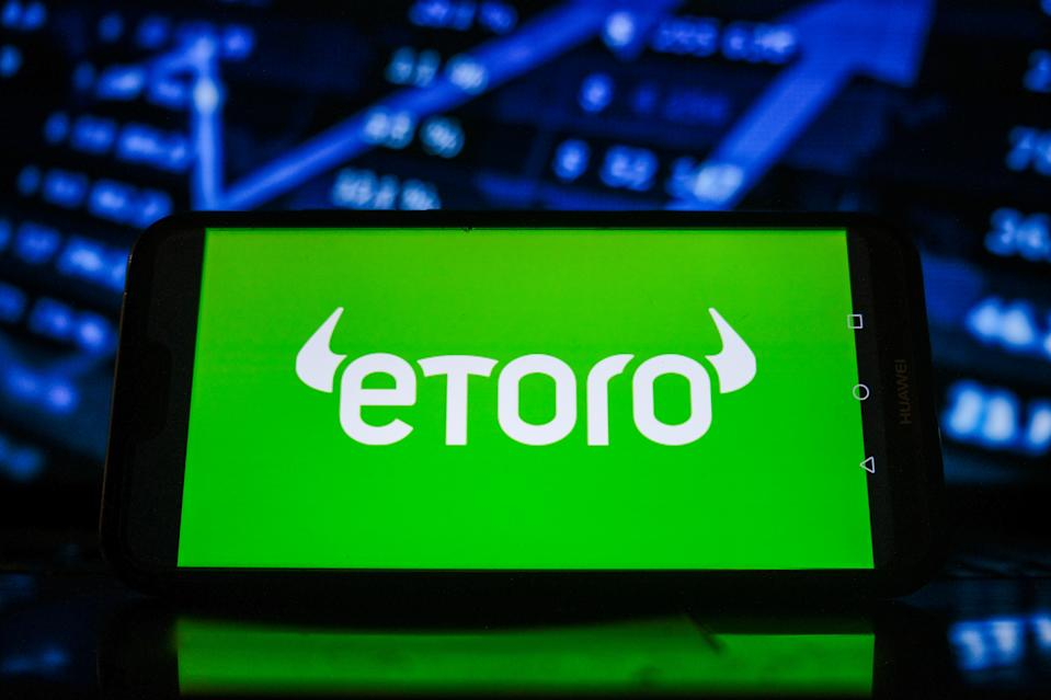 POLAND - 2021/02/08: In this photo illustration an Etoro logo seen displayed on a smartphone with the stock market graphic in the background. (Photo Illustration by Omar Marques/SOPA Images/LightRocket via Getty Images)