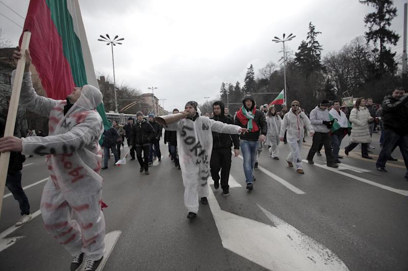 """Bulgarians shout slogans as they block the traffic at main road juncture during a protest against higher electricity and heating bills, in Sofia, Sunday, Feb. 17, 2013. Thousands of angry Bulgarians chanted """"mafia"""" and """"resignation"""" demanded the expulsion of the three foreign-controlled power distributors that control the local market: Czech Republic's CEZ and Energo-Pro, and Austria's EVN (AP Photo/Valentina Petrova)"""