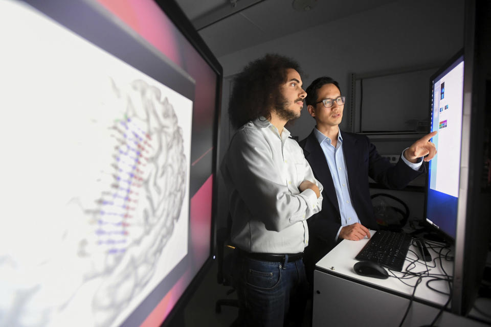 """In this Friday, June 7, 2019 photo provided by the University of California, San Francisco, Dr. Edward Chang, right, and postdoctoral scholar David Moses work at UCSF's Mission Bay campus. """"Most of us take for granted how easily we communicate through speech,"""" says Chang, a neurosurgeon UCSF. """"It's exciting to think we're at the very beginning of a new chapter, a new field"""" to ease the devastation of patients who lost that ability. (Noah Berger/UCSF via AP)"""