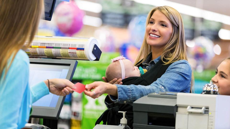 Mid adult Caucasian woman is shopping local grocery store or supermarket with elementary age daughter and infant, fees, America, money, payment, avoid fees, bills, debt