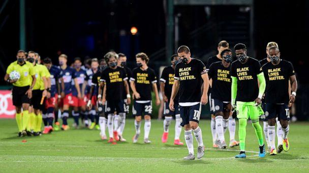PHOTO: Philadelphia Union and New England Revolution players walk on the pitch prior to their game during the knockout round of the MLS is Back Tournament at ESPN Wide World of Sports Complex, July 25, 2020, in Reunion, Florida. (Emilee Chinn/Getty Images)