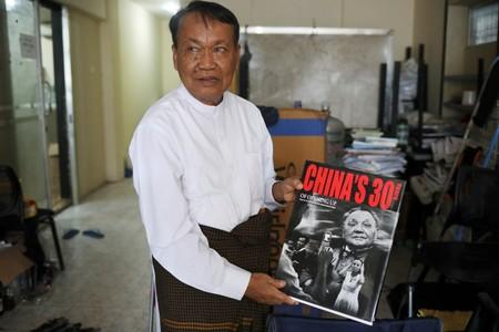 Monywa Aung Shin, Editor-in-Chief of D. Wave Journal, the magazine distributed by National League for Democracy Party (NLD), shows one of the books he got during his trip to China in his office in Yangon