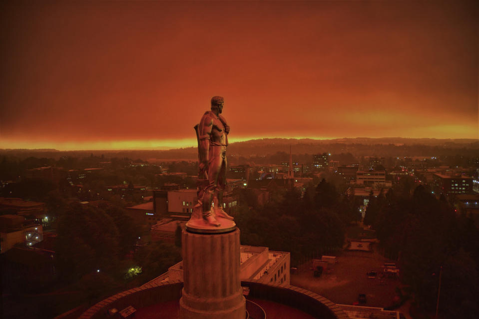 """This drone photo provided by Michael Mann shows the Oregon Capitol building, with its """"Oregon Pioneer"""" bronze sculpture atop the dome, with skies filled with smoke and ash from wildfires as a backdrop in Salem, Ore., on Sept. 8, 2020. Fires continued to rage across the West Coast on Monday, Sept. 21, 2020. (Michael Mann via AP)"""