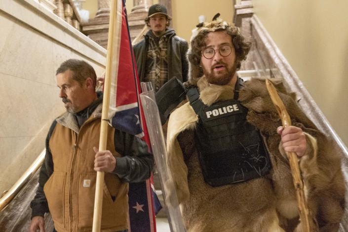 FILE - In this Jan. 6, 2021 file photo, insurrectionists loyal to President Donald Trump, including Aaron Mostofsky, right, and Kevin Seefried, left, walk down the stairs outside the Senate Chamber in the U.S. Capitol, in Washington. Prosecutors say Seefried, photographed carrying a Confederate battle flag during a deadly riot in the U.S. Capitol was arrested Thursday, Jan. 14, after authorities used the image to help identify him. (AP Photo/Manuel Balce Ceneta, File)