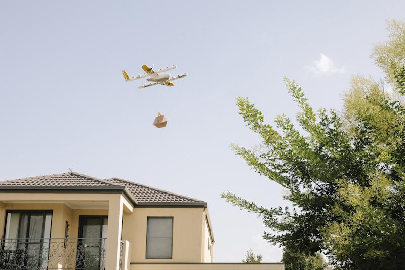 Wing drone delivering a package above a house