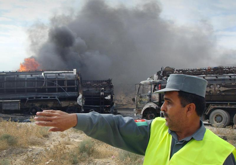 An Afghan police officer chats with a colleague, unseen, as NATO supply trucks burn in Samangan, north of Kabul, Afghanistan, Wednesday, July 18, 2012. Afghan officials say a magnetic bomb placed on a truck exploded and destroyed 22 NATO supply vehicles in northern Afghanistan. (AP Photo/Javed Basharat)