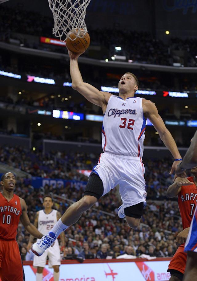 Los Angeles Clippers forward Blake Griffin, right, goes up for a dunk as Toronto Raptors guard DeMar DeRozan, left, looks on during the first half of an NBA basketball game, Friday, Feb. 7, 2014, in Los Angeles. (AP Photo/Mark J. Terrill)
