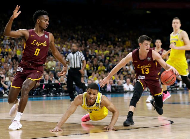 Michigan guard Jaaron Simmons, center, fights for a loose ball with Loyola Chicago's Donte Ingram, left, and Clayton Custer, right, during the first half in the semifinals of the Final Four NCAA college basketball tournament, Saturday, March 31, 2018, in San Antonio. (AP Photo/Eric Gay)